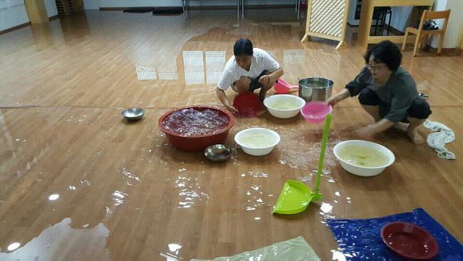 제천법당 조상인 님과 청주법당 박미자 님이 대야, 바가지 등 비를 담을 수 있는 그릇은 모두 총동원해 물을 퍼내고 있습니다.