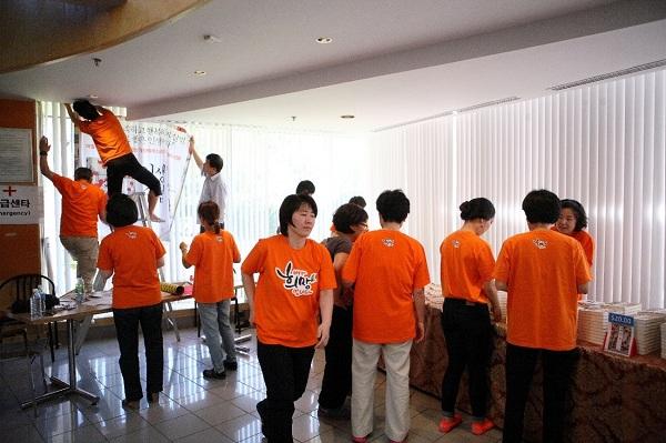 자원 봉사자들의 노력으로 성황리에 마친 희망세상만들기 강연. 행사에 앞서 강연장 로비에 배너를 달고 책 판매대를 꾸미고 있는 자원봉사자들