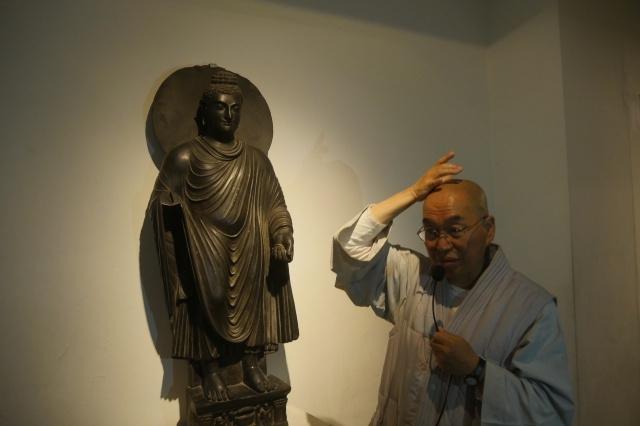 간다라 영향을 받은 불상의 모습을 보며 초기 불상의 형태에 대해 설명하는 스님