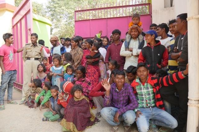 학교에 들어오지 못하고 문에 매달려 구경하는 마을 사람들