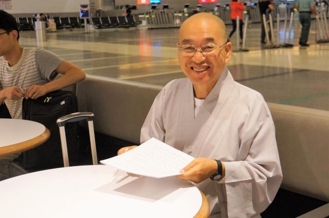 출국직전 공항에서 마지막 원고교정 마치고 활짝 웃는 스님