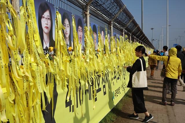 기억하겠습니다, 잊지 않겠습니다. 노란 리본이 물결처럼 달려있는 미수습자 9명의 사진 앞에서 한 소녀가 염원을 담아 리본을 달고 있습니다.